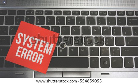 Concept Image of a red sticky note pasted on a keyboard with a message word white in color SYSTEM ERROR #554859055