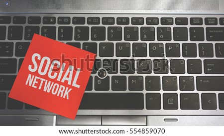 Concept Image of a red sticky note pasted on a keyboard with a message word white in color SOCIAL NETWORK #554859070