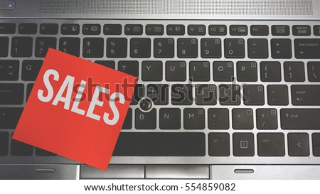 Concept Image of a red sticky note pasted on a keyboard with a message word white in color SALES #554859082