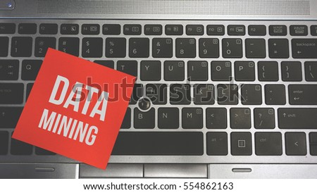Concept Image of a red sticky note pasted on a keyboard with a message word white in color DATA MINING #554862163
