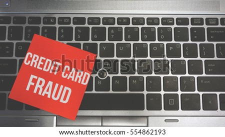 Concept Image of a red sticky note pasted on a keyboard with a message word white in color CREDIT CARD FRAUD #554862193