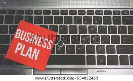 Concept Image of a red sticky note pasted on a keyboard with a message word white in color Business Plan #554862460
