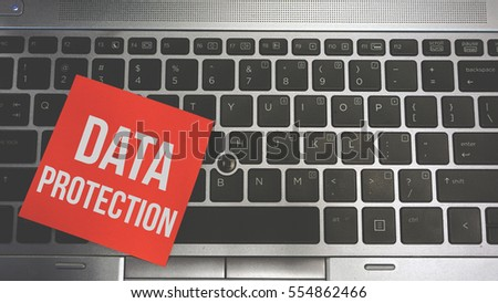 Concept Image of a red sticky note pasted on a keyboard with a message word white in color DATA PROTECTION #554862466