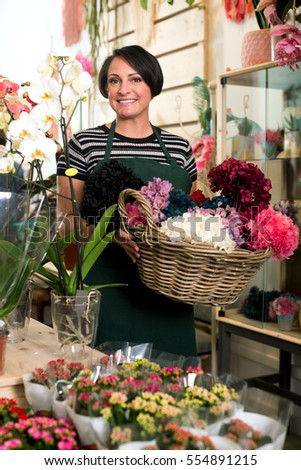 Mature female florist wearing an apron and happily working in the floral shop and smiling #554891215