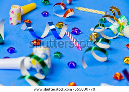 party decoration (colorful stars, party whistle and ribbon) in blue background