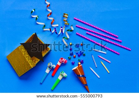 top view of party accessories with a miniature of confetti on blue background