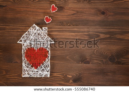 Home sweet home. Handmade home symbol with heart shape on wooden background with copy space #555086740
