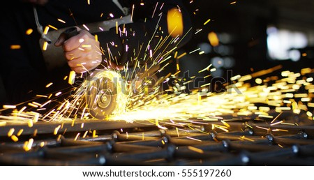 Industrial worker cutting metal with a lot of sharp sparks (extra close up) #555197260