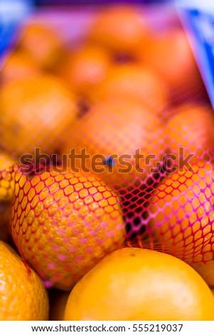 Closeup box of clementine mandarin oranges in red netting #555219037