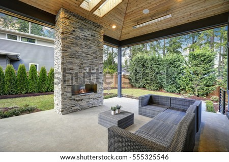 Chic, elegant deck patio design features vaulted paneled ceiling with skylights over a floor to ceiling gray stone fireplace and large taupe wicker sofa with ottoman as coffee table. Northwest, USA #555325546
