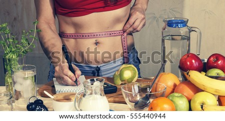 Young woman measures. Detox. Young girl measures the waist and uses proper nutrition. Detox drinks, ingredients, dumbbells. Concept: healthy lifestyle. #555440944
