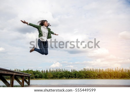 Happy young beautiful women jumping on the waterfront dock.  #555449599