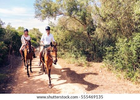 Young Tourist Couple Horseback Riding Royalty-Free Stock Photo #555469135