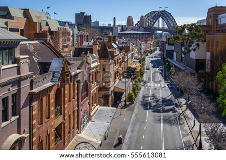 View of George Street in the Rocks, the historic district of Sydney. In the background, the harbour Bridge. Royalty-Free Stock Photo #555613081