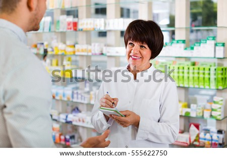 Smiling woman pharmacist in white coat helping customers to find item in drug store #555622750