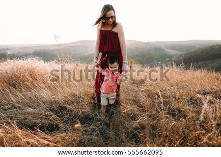 beautiful young mother in a long red dress easy walks with her young son. Summer, sunset, high yellow grass, mountains. He is on the hands, holding the hand #555662095