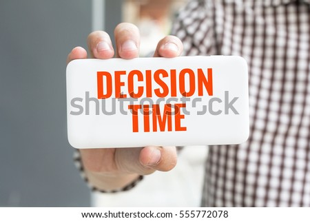 Man hand showing DECISION TIME word phone with  blur business man wearing plaid shirt.