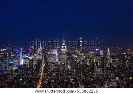 New york city, manhattan skyline at dusk or nighttime with dark cloudy sky and lights. The Empire State Building, Chrysler building and other Midtown high rises and skyscrapers. Cityscape. Urban.