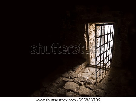 Arc fort passageway from cold damp Blackness to glow Light with rusted iron grate cell. Gaol rugged ominous shadow solid hallway with upward leading to day sunlight with space for text on sky backdrop #555883705