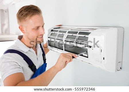 Happy Male Technician Repairing Air Conditioner With Screwdriver Royalty-Free Stock Photo #555972346