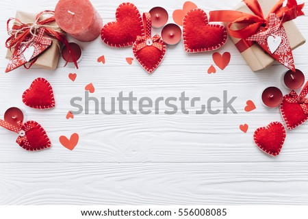 Wooden white background with red hearts, gifts and candles. The concept of Valentine Day. #556008085