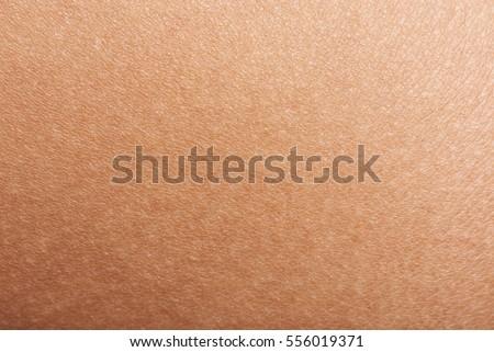 Dark skin of woman hand macro. Human skin texture background #556019371