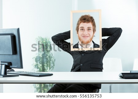 office worker with his arms relaxed and a picture frame with a photo of another face with a crazy expression