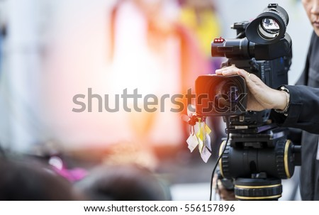 Video camera operator working with his equipment Royalty-Free Stock Photo #556157896