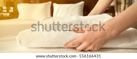Close-up of hands putting stack of fresh white bath towels on the bed sheet. Room service maid cleaning hotel room. Lens flair in sunlight. Horizontal photo banner for website header design #556166431