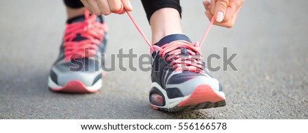 Female hands tying shoelace on running shoes before practice. Runner getting ready for training. Sport active lifestyle concept. Close-up. Horizontal photo banner for website header design
