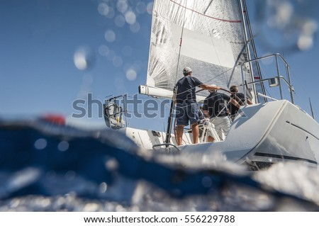 Aft of sailing boat with skipper from underwater view Royalty-Free Stock Photo #556229788