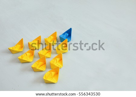 Leadership concept with paper boats on blue wooden background. One leader ship leads other ships. Filtered and toned image Royalty-Free Stock Photo #556343530