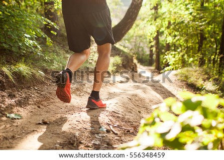 close up silhouette legs and feet of extreme cross country man running and training on rural track jogging at sunset with harsh sunlight and lens flare in countryside sport and healthy lifestyle #556348459
