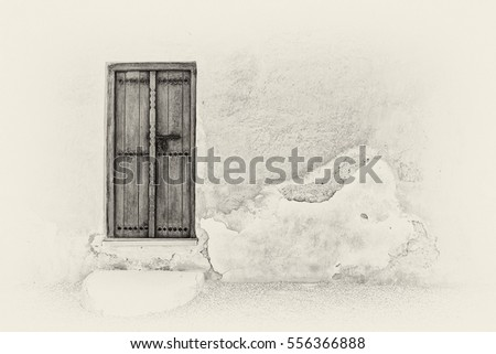 Sepia image of a traditional Arabian carved wooden door with a step in a crumbling plaster wall of a restored house in the Arabian Gulf. #556366888