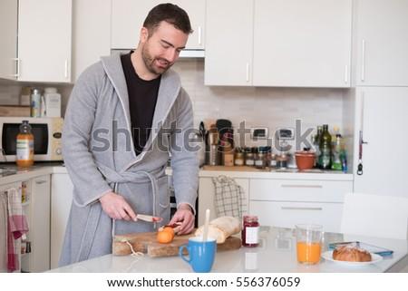 Cheerful man preparing an healthy breakfast in the morning #556376059