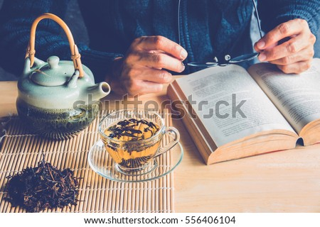 A man reading a book with cup of tea and tea pot #556406104