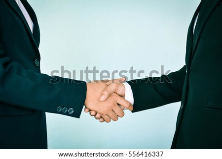 Businesswomen holding hand , selective of focus and blue background #556416337