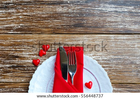 St Valentines Day place setting en white red tone. Plate, cutlery, line napkin, decorative heart on wooden background with copy space.  Love romantic dinner concept.  #556448737