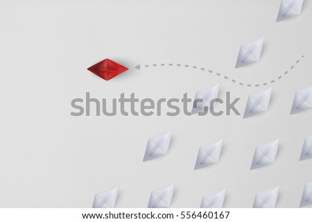 Business concept minimal as a group of paper ship in one direction and with one individual pointing in the different way as icon for innovative solution. #556460167
