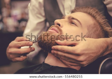 Side view of handsome bearded man having his beard cut by hairdresser at the barbershop #556480255