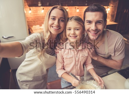 Cute little girl and her beautiful parents in aprons are doing selfie and smiling while baking in kitchen at home