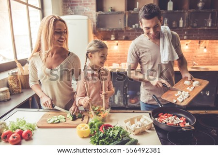 Cute little girl and her beautiful parents are  smiling while cooking in kitchen at home Royalty-Free Stock Photo #556492381
