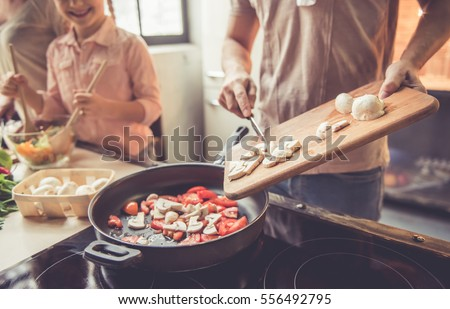 Cropped image of cute little girl and her beautiful parents cooking together in kitchen at home Royalty-Free Stock Photo #556492795