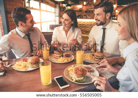 Business people are eating, talking and smiling while having lunch in cafe #556505005