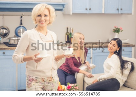 Toned picture of friends girls spending free time in company and having party at home. Pretty ladies drinking tea or coffee. Home party concept. #556514785