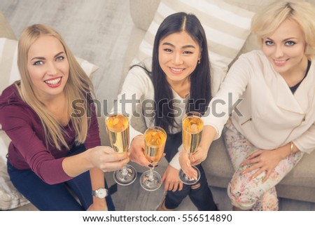 Toned top view picture of best friends girls drinking champagne while spending free time having party at home. Beautiful women smiling for camera. #556514890
