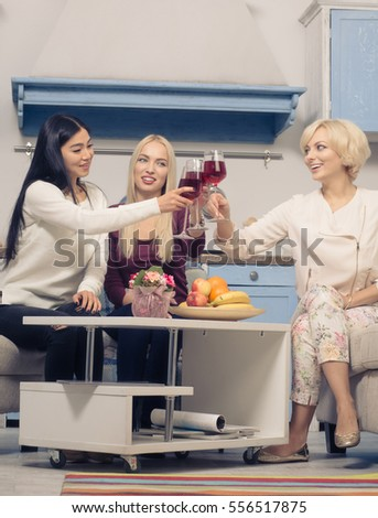 Toned low view picture of happy friends girls drinking red wine from glasses while spending free time at home. Friends party concept. #556517875