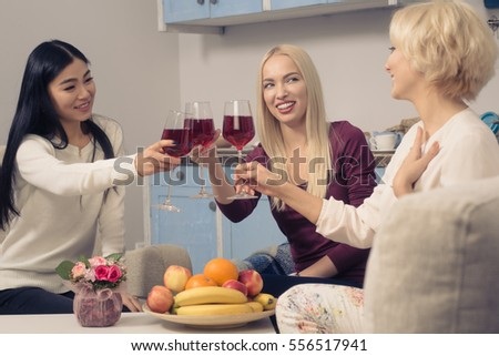 Toned picture of happy friends girls drinking red wine and smiling while spending free time at home. Beautiful cheerful ladies having party in kitchen after hard working day. #556517941