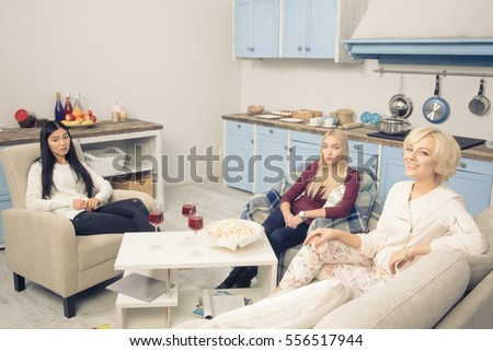 Toned picture of friends girls having round table with pop corn and alcohol drinks in kitchen while spending free time all together at home. Friends party concept. #556517944