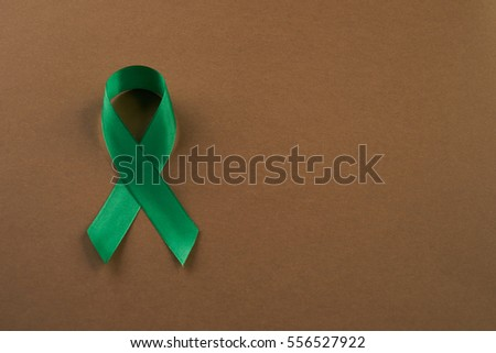 Green awareness ribbon on brown background. Symbol of Mental Health. Top vew with copy space #556527922